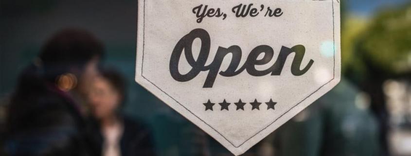 "A door sign saying ""Yes, we're open""."